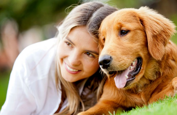 Portrait of a woman with her beautiful dog lying outdoors